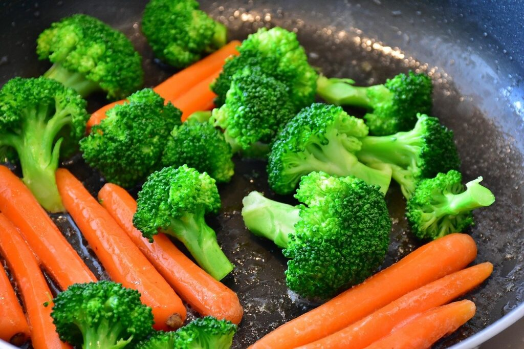 Cenouras e pedaços de brócolis em tigela marrom sendo lavadas