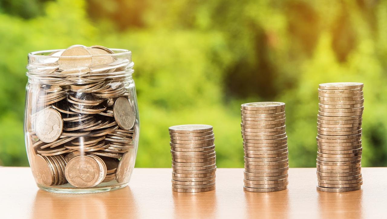 Pote transparente cheio de moedas e três pilhas pequenas de moedas sobre superfície de madeira com paisagem verde ao fundo