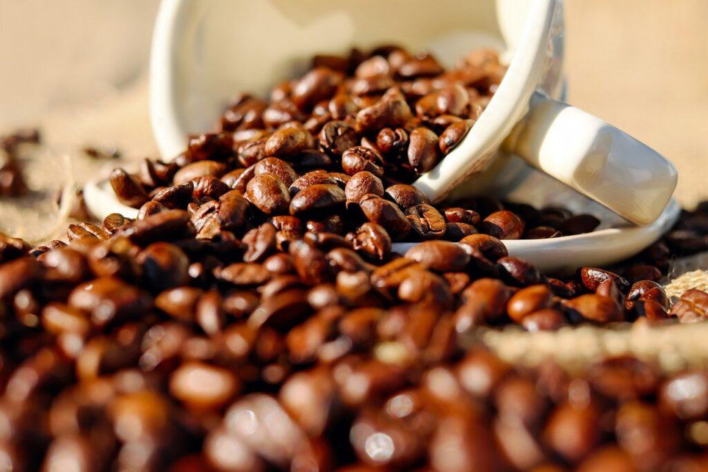 Grãos de café marrons espalhados em mesa por caneca branca