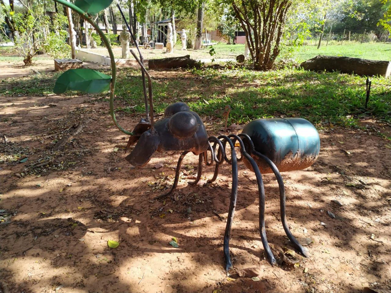 Escultura de formiga feita de ferragens exposta em sítio