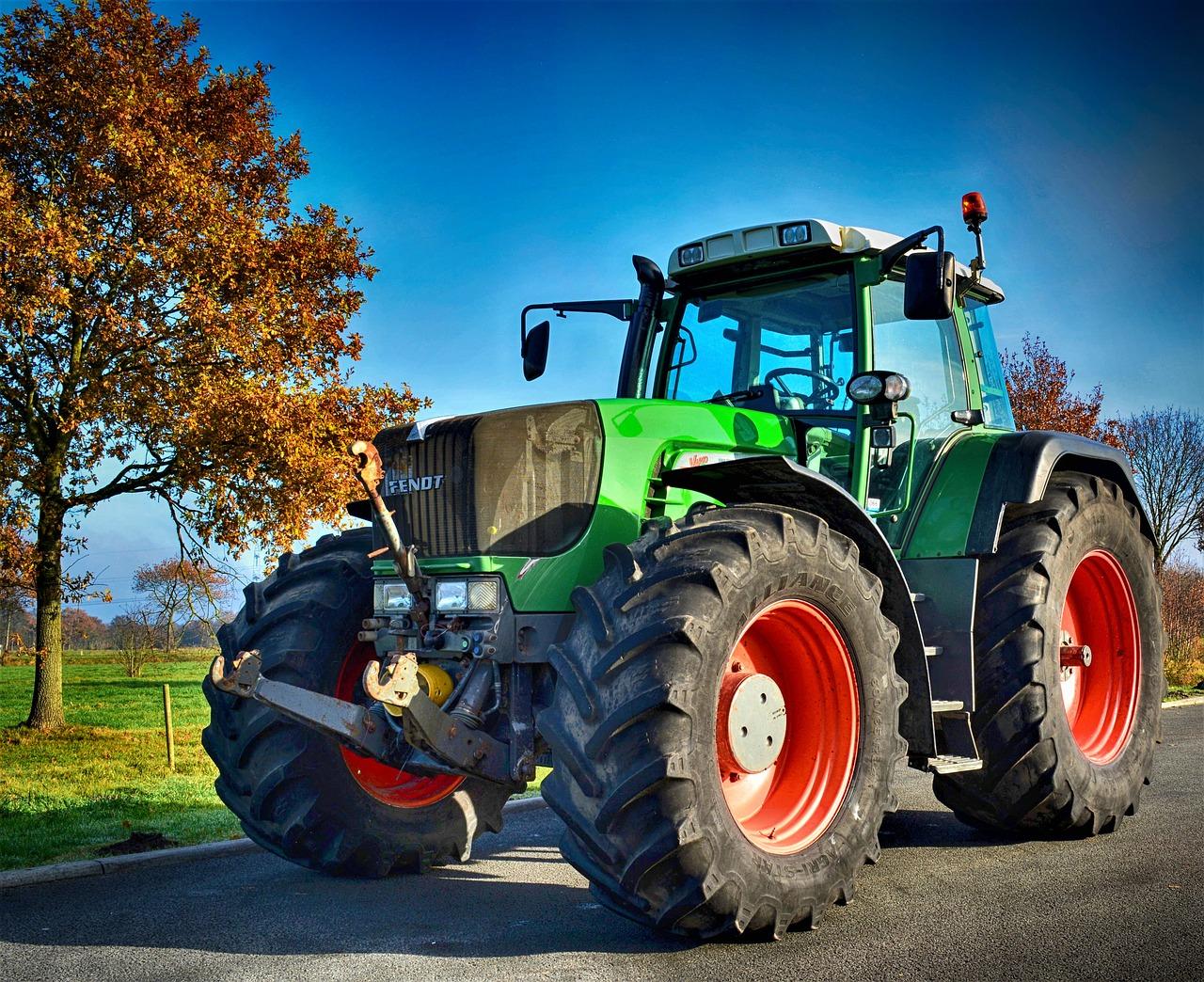 Trator verde, com rodas pretas em frente a campo verde