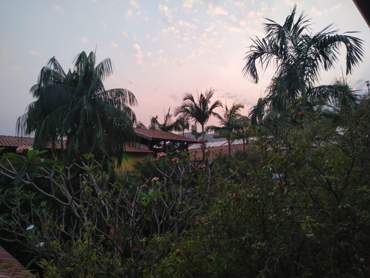 Pousada ao pôr-do-sol com árvores é opção para turismo rural